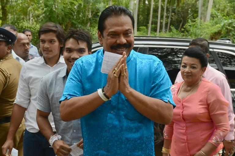 Former Sri Lankan president and parliamentary candidate Mahinda Rajapakse arrives with his family to cast his vote at a polling station in his native town of Tangalla on August 17, 2015