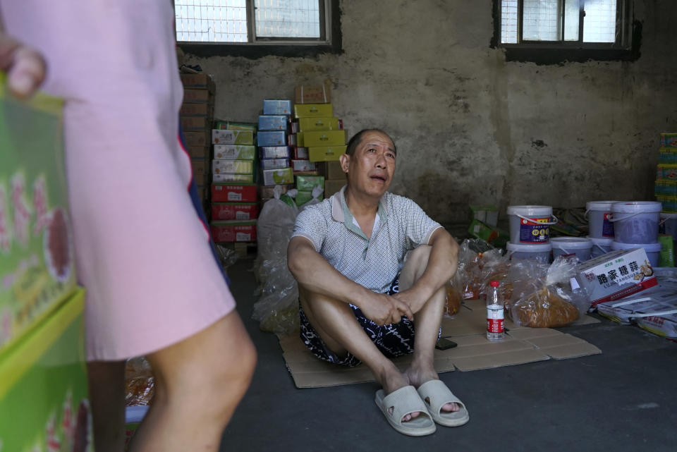 Lu Jinling sits in a family warehouse with pickled vegetables that he and his wife salvaged from the floods in Xinxiang in central China's Henan Province, Monday, July 26, 2021. Record rain in Xinxiang last week left the couple's goods in a nearby market underwater, causing losses that could run into the tens of thousands of dollars. Dozens of people died in the floods that immersed large swaths of central China's Henan province in water. (AP Photo/Dake Kang)