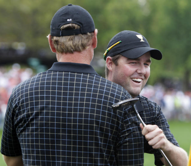International team player Marc Leishman, right, of Australia, hugs teammate Ernie Els, of South Africa, after putting on the 18th green during the single matches at the Presidents Cup golf tournament at Muirfield Village Golf Club Sunday, Oct. 6, 2013, in Dublin, Ohio. (AP Photo/Jay LaPrete)