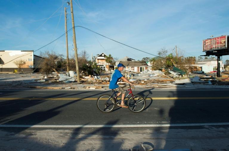 A man bikes past a destroyed gas station near Port Saint Joe, Florida