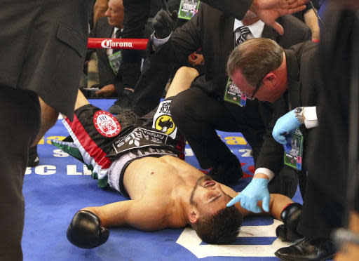 Carlos Ocampo is attended to after being knocked out by Errol Spence Jr. during the first round of an IBF welterweight title boxing match Saturday, June 16, 2018, in Frisco, Texas. (AP Photo/Richard W. Rodriguez)