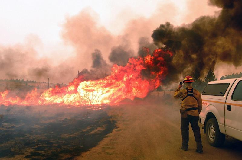 In this photo provided by the Madison County Disaster & Emergency Services, a firefighter stands ready at the 19 mile fire, Thursday, Aug. 30, 2012 between Madison County and Butte, Mont. Rapidly expanding wildfires across a broad swath of southern Montana have caused injuries and burned homes, buildings and vehicles, authorities said Thursday, as firefighters struggled to contain the flames amid hazardous conditions. (AP Photo/Madison County Disaster & Emergency Services, Steve DiGiovanna)