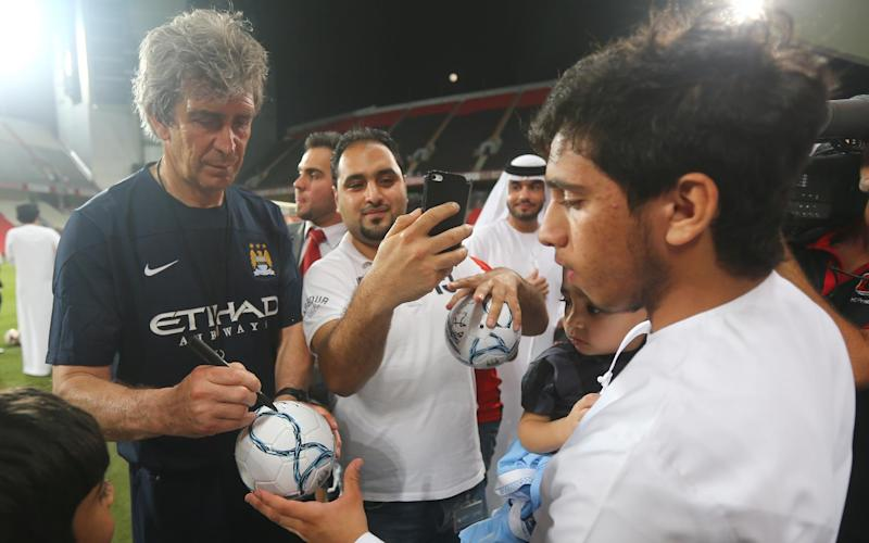 Manchester City manager Manuel Pellegrini autographs a ball for a fan during a team training session at the Sheikh Mohammed Bin Zayed Stadium in Abu Dhabi, on May 14, 2014