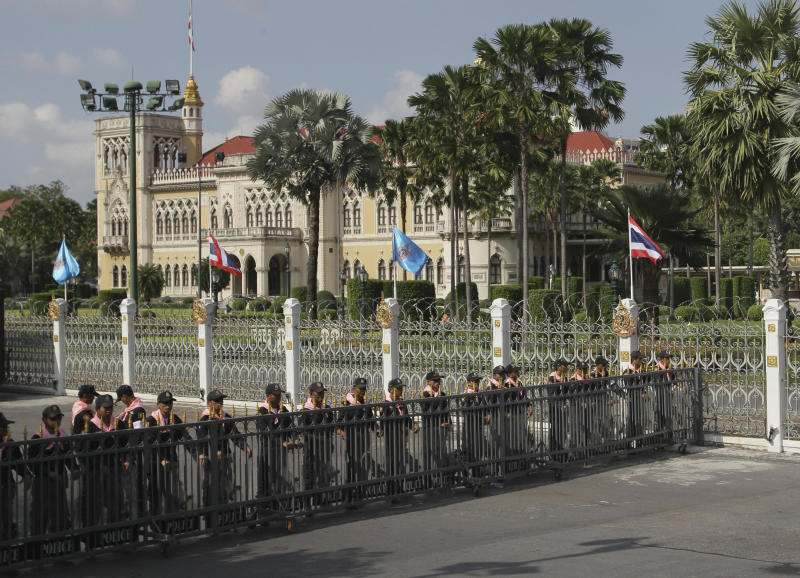 Thai policemen guard in front of fense set up to block the way in Government House in Bangkok, Friday, Nov. 23, 2012. Anti-government protesters are expected to show up in Bangkok on Saturday to demand an overthrow of the current government under the rule of Prime Minister Yingluck Shinawatra. (AP Photo/Sakchai Lalit)