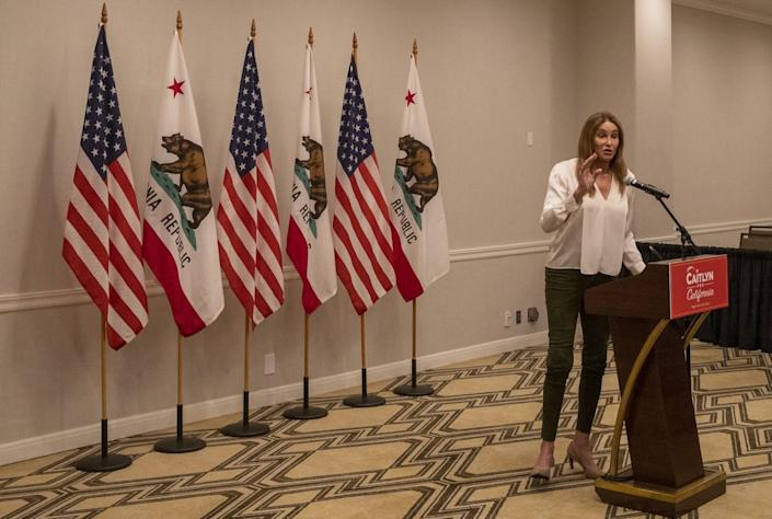 Caitlyn Jenner stands in front of a row of flags at a lectern