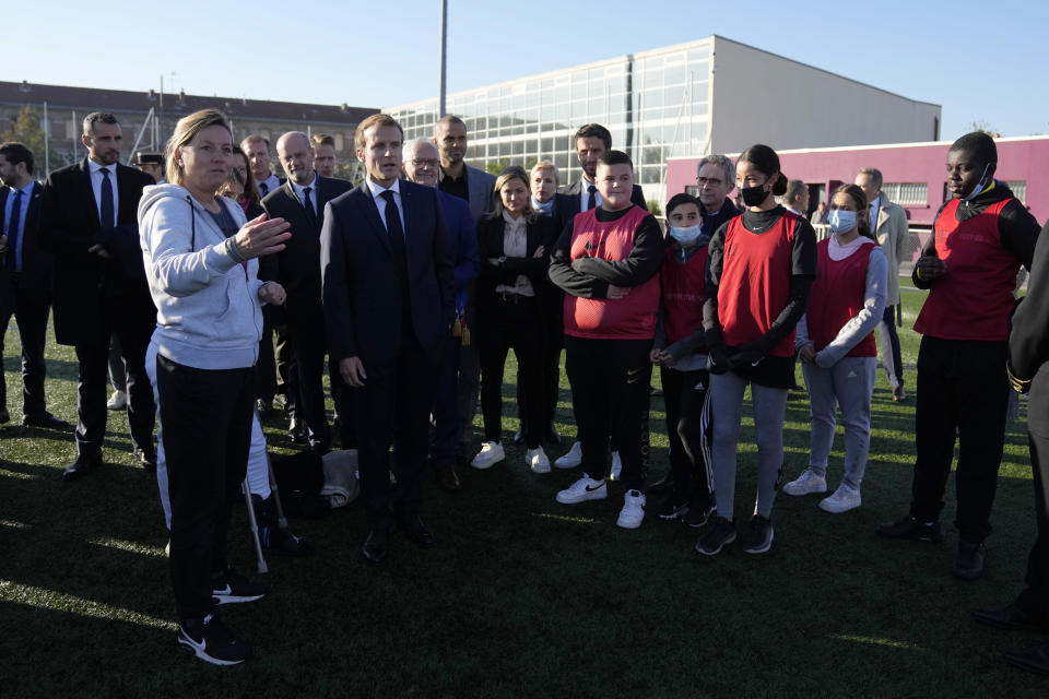 French President Emmanuel Macron, center, meets youth on a stadium in Tremblay-en-France, outside Paris, Thursday, Oct.14, 2021. French President Emmanuel Macron will promote sports ahead of the 2024 Olympic Games in Paris. (AP Photo/Francois Mori, Pool)