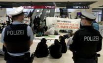 Activists block an escalator to protest against the opening of the new Berlin-Brandenburg-Airport 'Willy Brandt' in Berlin, Germany, Saturday, Oct. 31, 2020. Berlin's new airport opens after years of delays and cost overruns. (AP Photo/Michael Sohn)