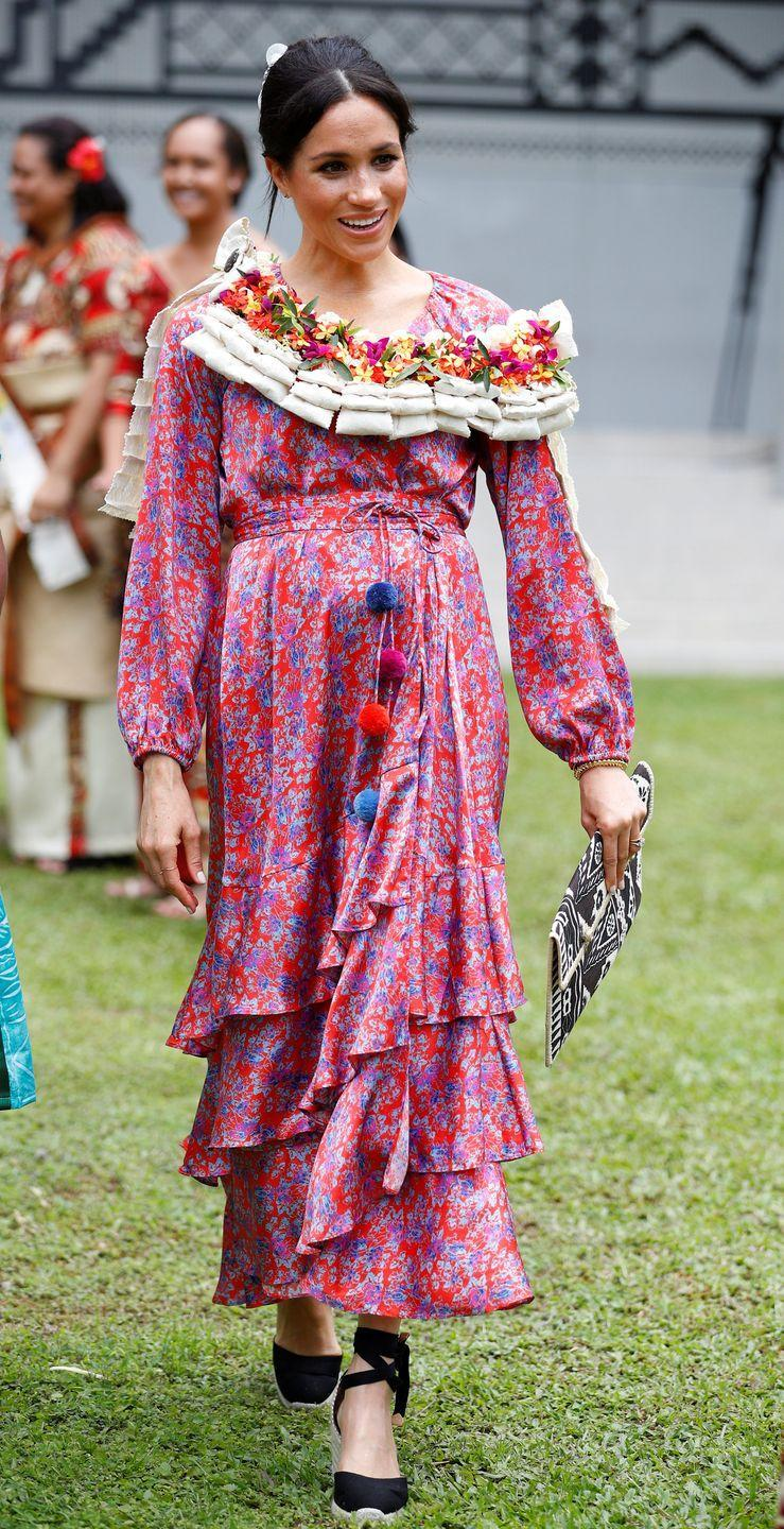 <p>Shortly after announcing her first pregnancy in October 2018, Meghan Markle visited the University of the South Pacific in Suva, Fiji. She wore a tiered red and purple maxi dress, black espadrilles, and traditional honorary garb. </p>