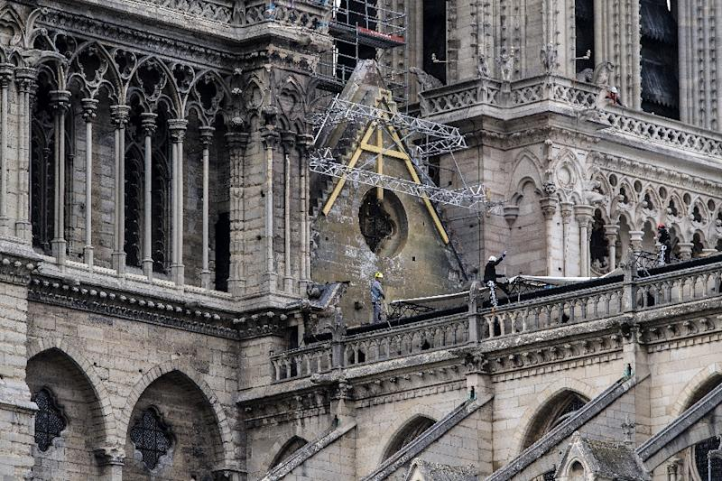 Workers installed tarps over the roof of Notre-Dame, two-thirds of which was left exposed by the fire damage sustained last week (AFP Photo/Christophe ARCHAMBAULT)