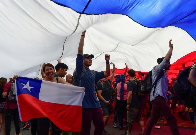 People protest under a giant Chilean national flag in Santiago, on October 25 (AFP Photo/Martin BERNETTI )