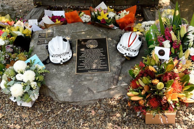 Flowers and the helmets of volunteer firefighters O'Dwyer and Keaton are seen at a memorial at the Horsley Park Rural Fire Brigade in Horsley Park