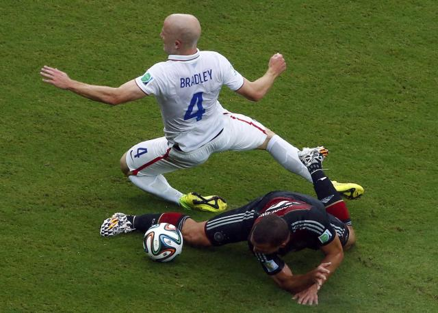 REFILE - CORRECTING HEADLINE Michael Bradley of the U.S. falls over Germany's Lukas Podolski during their 2014 World Cup Group G soccer match at the Pernambuco arena in Recife June 26, 2014. REUTERS/Ruben Sprich (BRAZIL - Tags: SOCCER SPORT WORLD CUP)