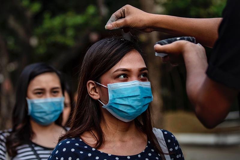 PARANAQUE, PHILIPPINES - FEBRUARY 26: Catholic devotees wearing protective masks fall in line to have their head sprinkled with ash during Ash Wednesday services at a church on February 26, 2020 in Paranaque city, Metro Manila, Philippines. The Philippines Catholic Church has recommended sprinkling ash on the heads of devotees, rather than the usual practice of rubbing it on foreheads, to avoid physical contact as a precaution against COVID-19. The first COVID-19 death outside of China was reported in the Philippines last February 2, while the country has reported only 3 confirmed cases of the coronavirus so far. With over 78,000 confirmed cases around the world, the virus has so far claimed over 2,700 lives. (Photo by Ezra Acayan/Getty Images)