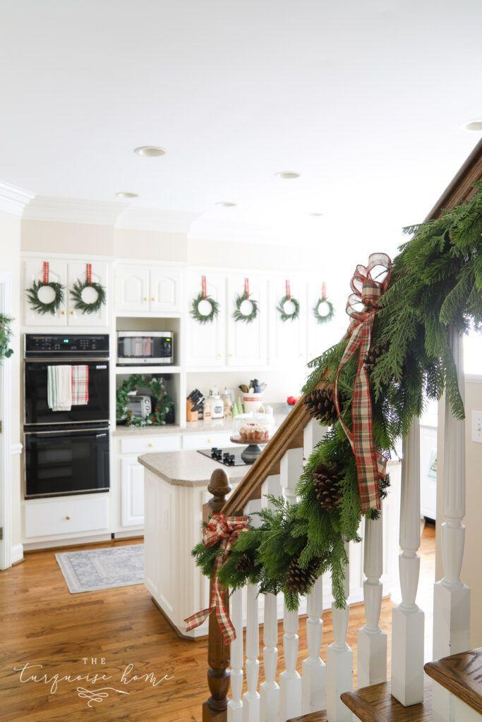 """<p>Simple garland with plaid ribbons to tie it in place is perfect in the kitchen. The pine cones add a nice rustic touch, especially welcome in a farmhouse kitchen. </p><p><strong>See more at <a href=""""https://theturquoisehome.com/traditional-christmas-kitchen-decorating-ideas/"""" rel=""""nofollow noopener"""" target=""""_blank"""" data-ylk=""""slk:The Turquoise Home."""" class=""""link rapid-noclick-resp"""">The Turquoise Home.</a></strong></p><p><a class=""""link rapid-noclick-resp"""" href=""""https://www.amazon.com/Christmas-Ribbon-Wrapping-Crafts-Supplies/dp/B07XP5D3JL/ref=sr_1_2_sspa?dchild=1&keywords=red+plaid+ribbon&qid=1633171989&sr=8-2-spons&psc=1&spLa=ZW5jcnlwdGVkUXVhbGlmaWVyPUFaR0xGR1dBQjNIUlkmZW5jcnlwdGVkSWQ9QTA0NTc5MjZaR1BYTzhERVlRR1cmZW5jcnlwdGVkQWRJZD1BMDA3MDIxNlJYSzRKSktJREpGWiZ3aWRnZXROYW1lPXNwX2F0ZiZhY3Rpb249Y2xpY2tSZWRpcmVjdCZkb05vdExvZ0NsaWNrPXRydWU%3D&tag=syn-yahoo-20&ascsubtag=%5Bartid%7C2164.g.37723896%5Bsrc%7Cyahoo-us"""" rel=""""nofollow noopener"""" target=""""_blank"""" data-ylk=""""slk:SHOP RED PLAID RIBBON"""">SHOP RED PLAID RIBBON</a></p>"""