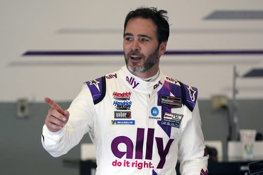 Jimmie Johnson interacts with crew members in his garage during a practice session for the Rolex 24 hour auto race at Daytona International Speedway, Saturday, Jan. 23, 2021, in Daytona Beach, Fla. (AP Photo/John Raoux)