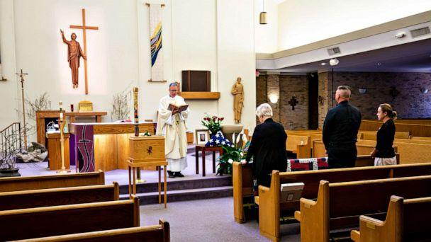 PHOTO: Father Sandy McDonald presides over the funeral of Ralph Ray, 73, at St. John Neumann Catholic Church in Columbia, SC., March 27, 2020. (Jeff Blake/USA TODAY NETWORK)