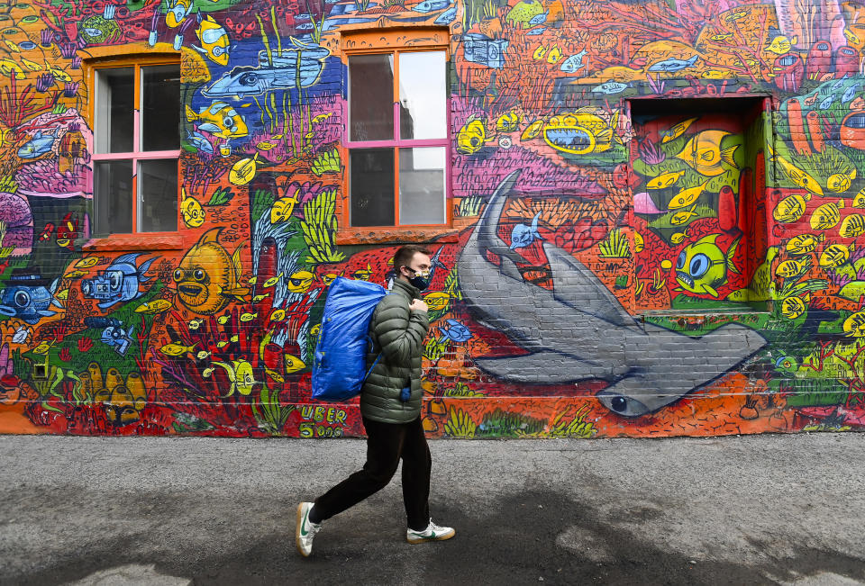 A person walks past a nature mural on Earth Day during the COVID-19 pandemic in Toronto, Thursday, April 22, 2021. (Nathan Denette/The Canadian Press via AP)