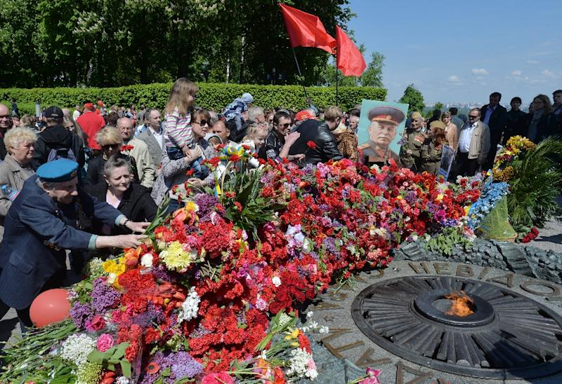 People lay flowers at the Tomb of the Unknown Soldier in Kiev on May 9, 2015, during a ceremony marking the 70th anniversary of the end of WWII iu Europe (AFP Photo/Genya Savilov)