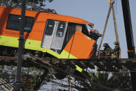 Firefighters work to lower to the ground a subway car dangling from a collapsed elevated section of the metro, in Mexico City, Tuesday, May 4, 2021. The elevated section of Mexico City's metro collapsed late Monday killing at least 23 people and injuring at least 79, city officials said. (AP Photo/Fernando Llano)