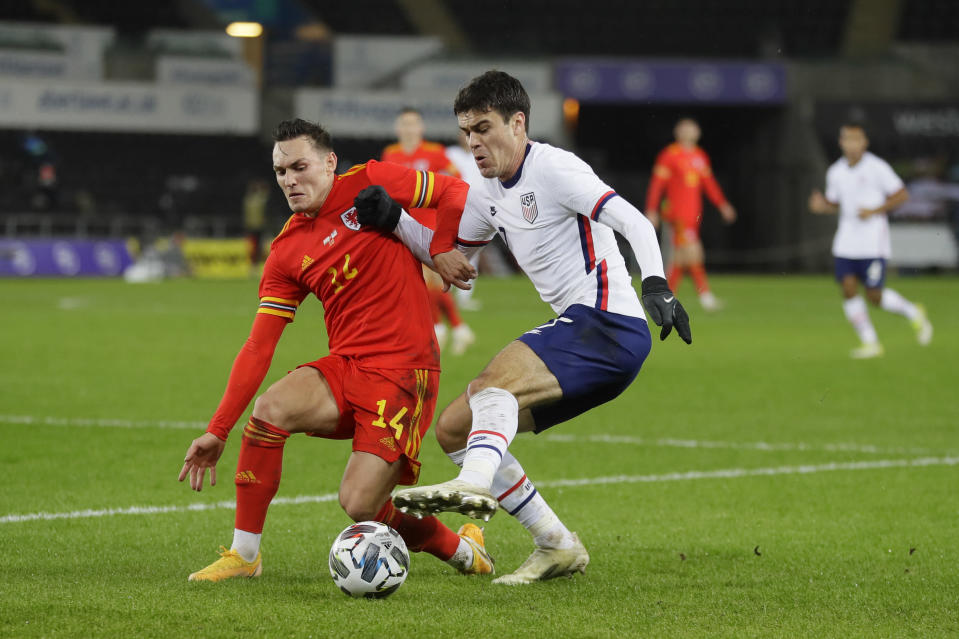 United States' Gio Reyna, right, vies for the ball with Wales' Rabbi Matondo during the international friendly soccer match between Wales and USA at Liberty stadium in Swansea, Wales Thursday, Nov. 12, 2020. (AP Photo/Kirsty Wigglesworth)