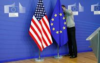FILE PHOTO: A worker adjusts EU and U.S. flags at the start of the 2nd round of EU-US trade negociations at the EU Commission headquarters in Brussels