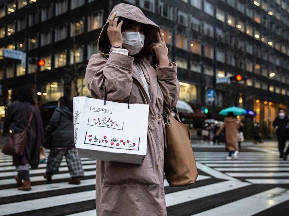 File: A woman wearing a face mask crosses a road on in Tokyo (Getty Images/ Representative image)