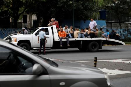 People ride in a tow truck during a blackout in Caracas