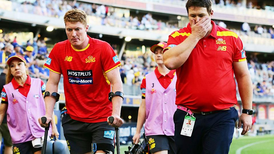 Matt Rowell, pictured here leaving the field with Gold Coast coach Stuart Dew.