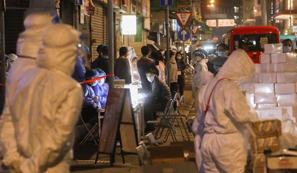 Government workers in protective gear filled Yau Ma Tei amid a lockdown that began on Tuesday night. Photo: Sam Tsang