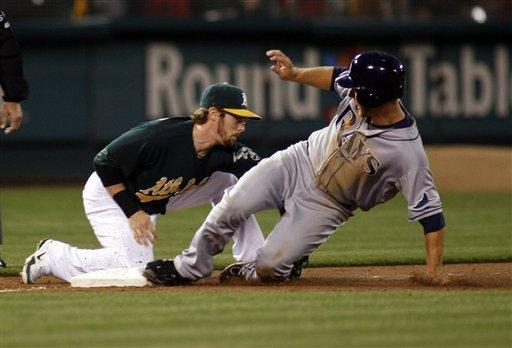 Tampa Bay Rays Ben Zobrist is safe at third as the Oakland Athletics Eric Sogard in the sixth inning of a baseball game in Oakland, Calif., Tuesday, July 31, 2012. (AP Photo/Dino Vournas)
