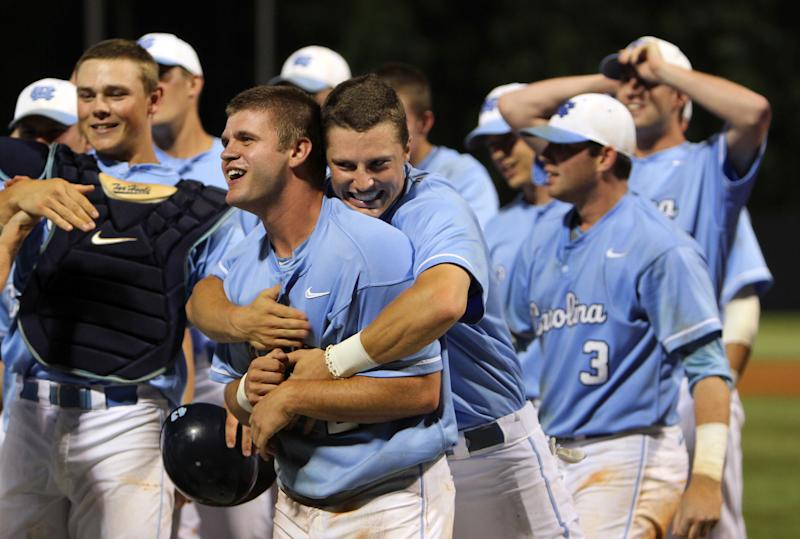 North Carolina's Skye Bolt hugs teammate Chaz Frank from behind, celebrating their 12-11 win in 13 innings over Florida Atlantic in the NCAA college regional championship baseball game in Chapel Hill, N.C., Monday, June 3, 2013. (AP Photo/Ted Richardson)