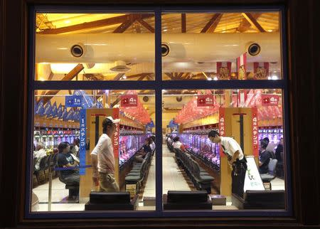 People are seen through windows at a Dynam pachinko parlour in Honjo, north of Tokyo August 4, 2014. REUTERS/Issei Kato