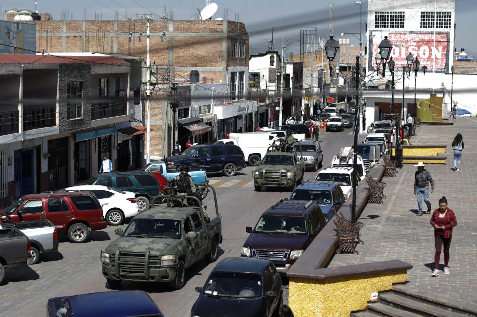 FILE - In this Feb. 10, 2020 file photo, National Guard patrol vehicles drive through the central square in Apaseo el Alto, Guanajuato state, Mexico. The two most powerful drug cartels in the hemisphere are battling over this industrial and farming hub of central Mexico — a state that has attracted gangs for the same reason it has lured auto manufacturers: road and rail networks that lead straight to the U.S. border. (AP Photo/Rebecca Blackwell, File)
