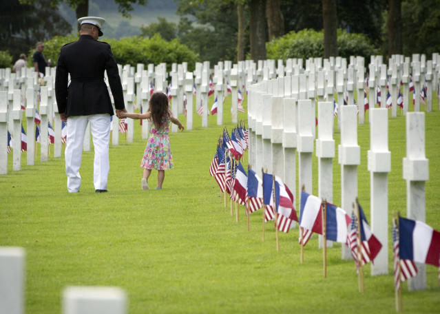 <p>A U.S. Marine Corps soldier walks with a small girl through headstones prior to a Memorial Day commemoration at the Aisne-Marne American Cemetery in Belleau, France, Sunday, May 27, 2018. The cemetery contains more that 2,000 American dead. (Photo: Virginia Mayo/AP) </p>