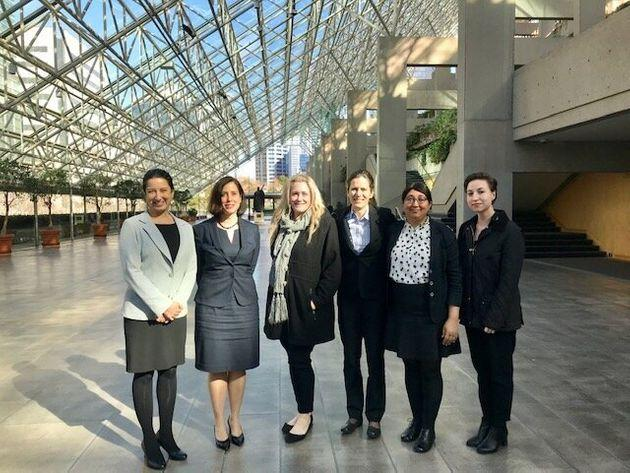 Nicole Bell, centre, and Raji Mangat, second from right, pose at a British Columbia courthouse.