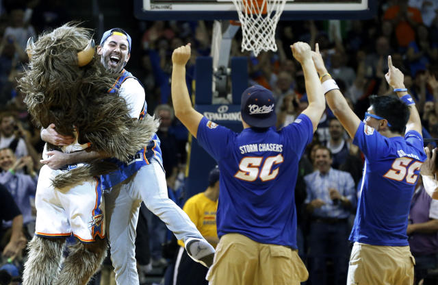 FILE - In this Monday, Nov. 18, 2013, file photo, Cameron Rodriguez, second from left, celebrates with Oklahoma City Thunder mascot Rumble, left, after hitting a half-court shot to win $20,000 during a timeout of an NBA basketball game between the Thunder and the Denver Nuggets in Oklahoma City. Rodriguez may not be able to keep both the money and his eligibility to compete in college athletics. (AP Photo/Sue Ogrocki, File)