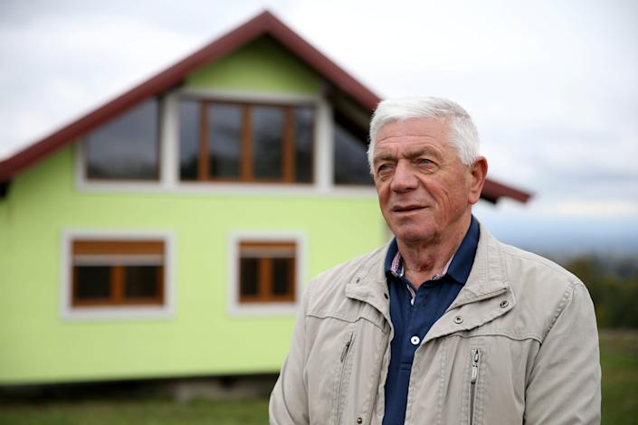 Vojin Kusic's stands in front of his rotating house, with its green façade and red metal roof, can rotate a full circle in the town of Srbac, northern Bosnia, Sunday, Oct. 10, 2021. It's a cloudy day.