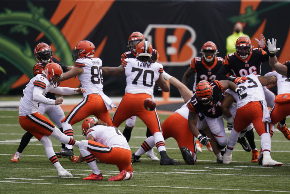 Cleveland Browns kicker Cody Parkey (2) boots a field goal out of the hold of Jamie Gillan (7) during the first half of an NFL football game against the Cincinnati Bengals, Sunday, Oct. 25, 2020, in Cincinnati. (AP Photo/Michael Conroy)