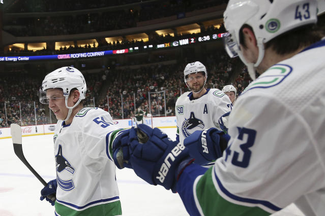 Vancouver Canucks' Troy Stecher, left, high-fives teammate Quinn Hughes after scoring a goal against the Minnesota Wild in the second period of an NHL hockey game Sunday, Jan. 12, 2020, in St. Paul, Minn. (AP Photo/Stacy Bengs)