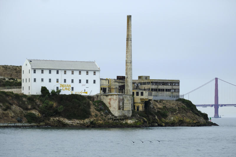 """In this photo taken Friday, Nov. 15, 2019, the words """"Indian Land"""" are painted on a building on Alcatraz Island with the Golden Gate Bridge in the background in San Francisco. The week of Nov. 18, 2019, marks 50 years since the beginning of a months-long Native American occupation at Alcatraz Island in the San Francisco Bay. The demonstration by dozens of tribal members had lasting effects for tribes, raising awareness of life on and off reservations, galvanizing activists and spurring a shift in federal policy toward self-determination. (AP Photo/Eric Risberg)"""