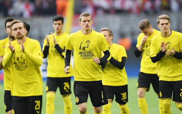 <span>Dortmund's players warm up with messages of support for defender Marc Bartra, who was taken to hospital following last night's attack</span> <span>Credit: PATRIK STOLLARZ/AFP </span>