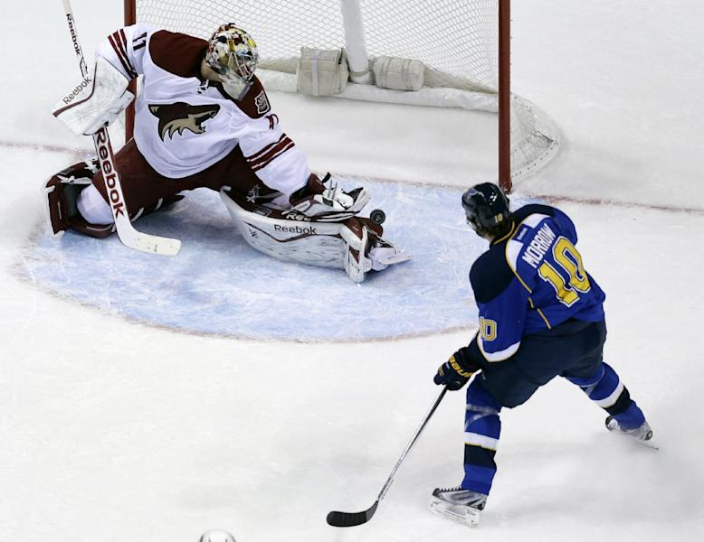 Phoenix Coyotes goalie Mike Smith, left, deflects a puck away from the net as St. Louis Blues' Brenden Morrow stands by during the third period of an NHL hockey game Tuesday, Nov. 12, 2013, in St. Louis. The Coyotes won 3-2 in overtime. (AP Photo/Jeff Roberson)