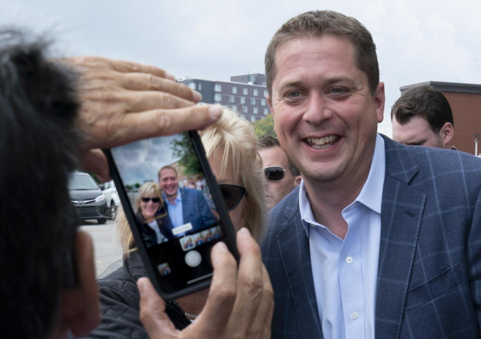 A supporter has a photo taken with Conservative leader Andrew Scheer at a campaign rally in Trois-Rivieres, Que. on Wednesday, September 11, 2019. THE CANADIAN PRESS/Paul Chiasson/The Canadian Press via AP)