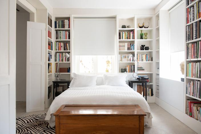 The main bedroom is an intimate studio nook on the second floor, with exposed concrete flooring, a hand-painted wooden library dressed in white oil paint, and a constantly revolving collection of design and cookbooks.