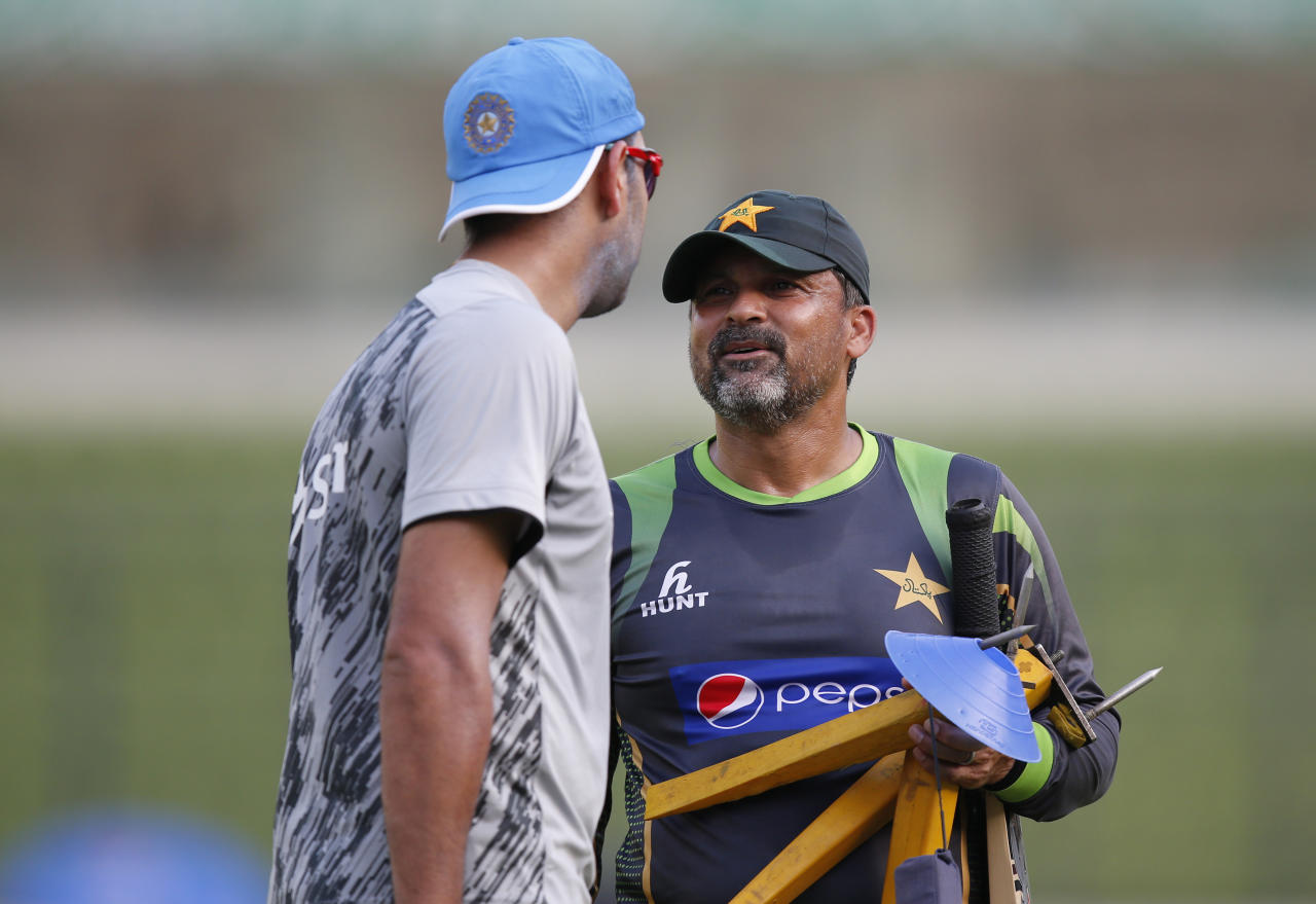 Pakistan cricket team coach Moin Khan, right, talks to India's cricketer Yuvraj Singh during a training session ahead of their ICC Twenty20 Cricket World Cup match in Dhaka, Bangladesh, Thursday, March 20, 2014. (AP Photo/Aijaz Rahi)