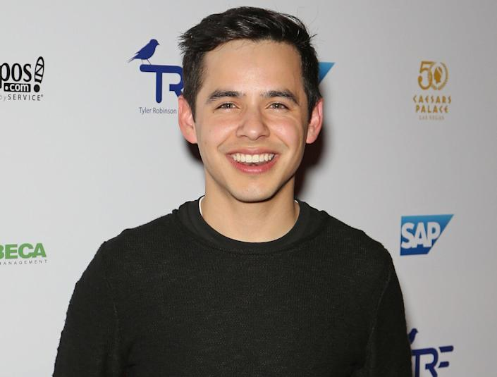 David smiles and wears a plain black long sleeve shirt at an event