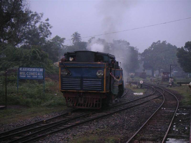 The 'X' Class steam Rack Locomotive arrives from its shed to take charge of the 662SR up to Coonoor while a signboard welcomes passengers to the Nilgiri Mountain Railway.