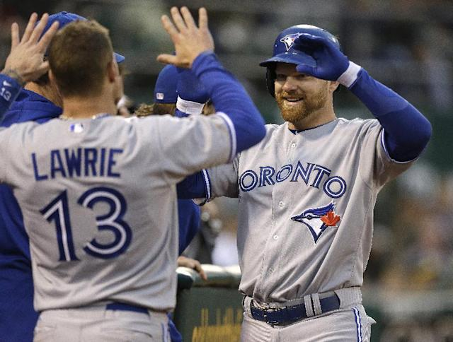 Toronto Blue Jays' Adam Lind, right, is congratulated by Brett Lawrie (13) after Lind hit a home run off Oakland Athletics' A.J. Griffin in the fifth inning of a baseball game Monday, July 29, 2013, in Oakland, Calif. (AP Photo/Ben Margot)
