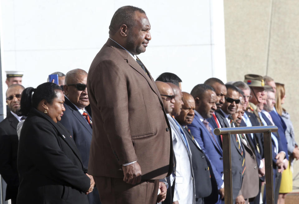 Papua New Guinea Prime Minister James Marape stands on a podium before inspecting troops as he is officially welcomed to Australia's Parliament House in Canberra Monday, July 22, 2019. Marape says his country's relationship with China in not open to discussion during his current visit to Australia. (AP Photograph/Rod McGuirk)
