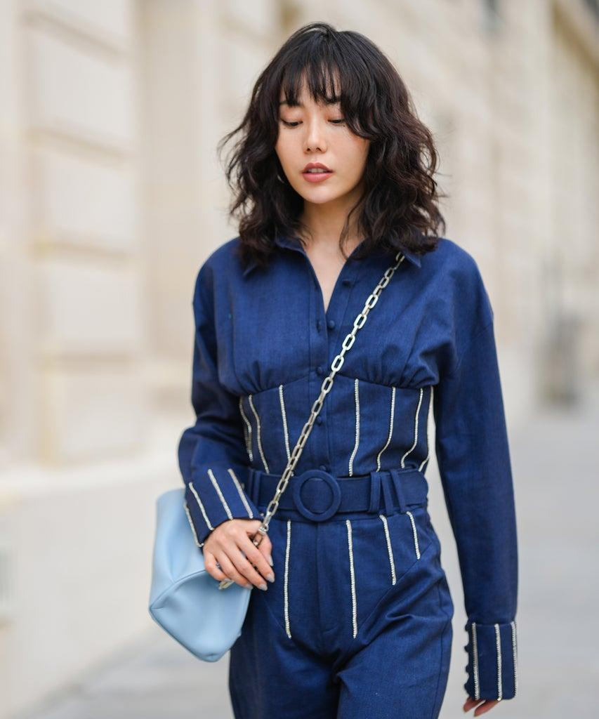 PARIS, FRANCE – SEPTEMBER 19: Fashion blogger Xiayan wears black sunglasses, silver earrings, a navy blue denim jumpsuit with white rhinestones embroidered straps on the belt and wrists, a pale blue shiny leather crossbody bag, during a street style fashion photo session, on September 19, 2021 in Paris, France. (Photo by Edward Berthelot/Getty Images)